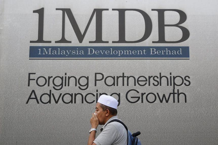A man walking past a 1MDB billboard at the funds flagship Tun Razak Exchange development in Kuala Lumpur, Malaysia.