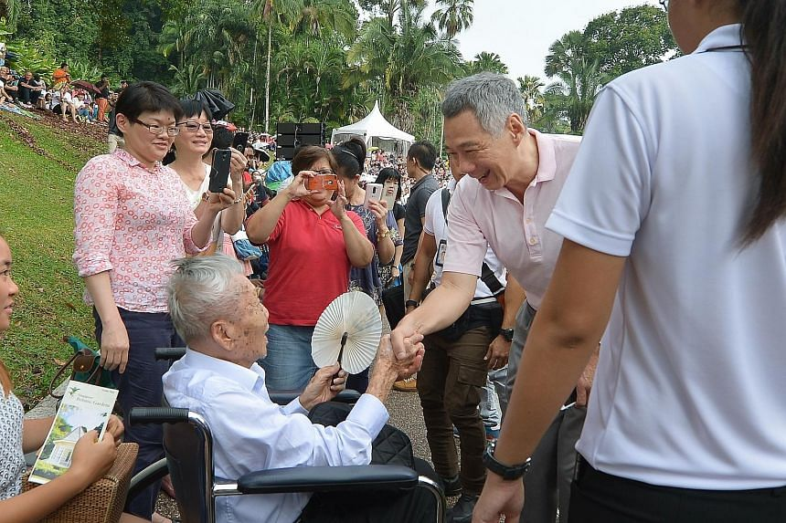 Prime Minister Lee Hsien Loong chatting with 101-year-old Mr Heng Kok Kai, a retired photographer, as Mr Heng's daughter Betty (in red top) snapped a photo of them, at the Botanic Gardens yesterday. Mr Heng, who enjoys music and being out among the l