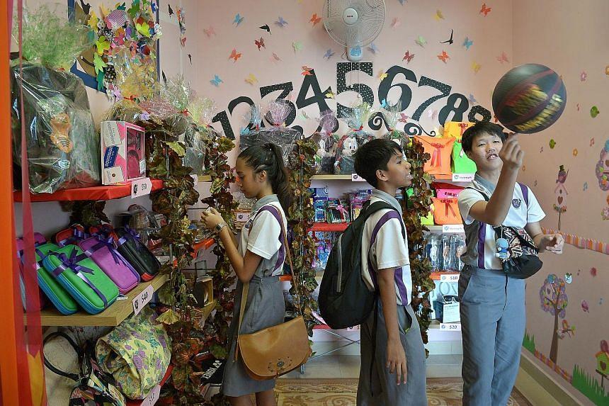 "NorthLight School students (from left) Sharvonne Sherrell Surash, 14, Farish Muhd Khair Farish Khalid, 13, and Amos Tay, 15, at the school's ""Life Shop"", where students can buy items with ""sticker money""."