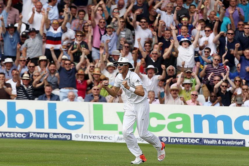 England fielder Stuart Broad celebrates after taking a catch to dismiss Australian batsman David Warner for 64.
