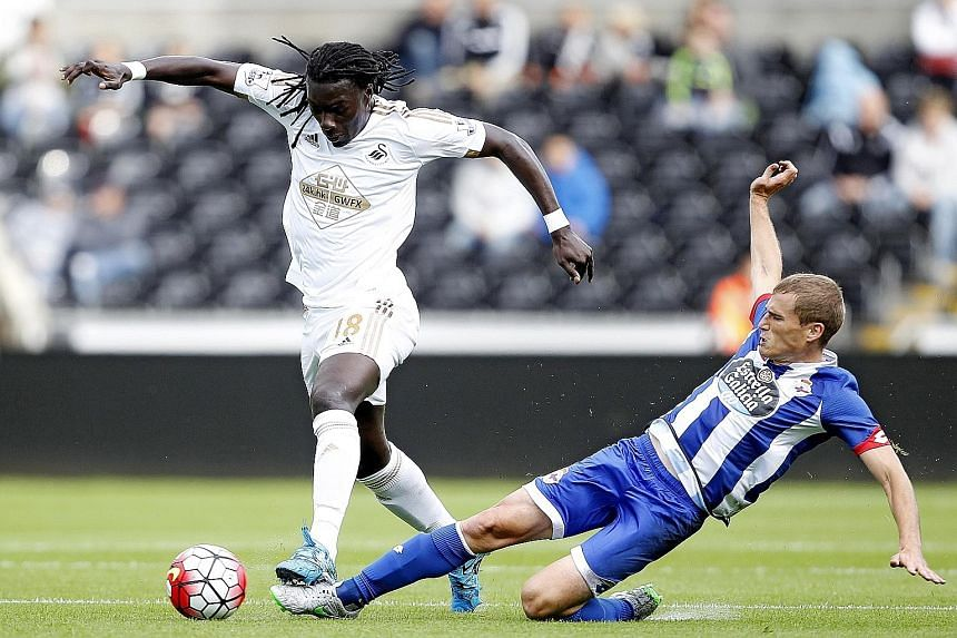 Bafetimbi Gomis (left), Swansea City's top scorer last season with 10 goals, in action against Alex Bergantinos of Deportivo La Coruna in a pre-season friendly. Swansea finished eighth in the EPL last term but will have their work cut out at Stamford