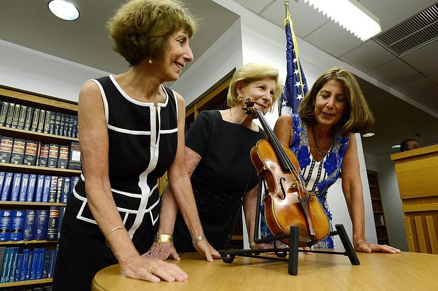 Sisters (from left) Jill, Nina and Amy Totenberg with the Ames Stradivarius violin at a press conference at a New York Justice Department office on Thursday. The violin was stolen in 1980 from their father.