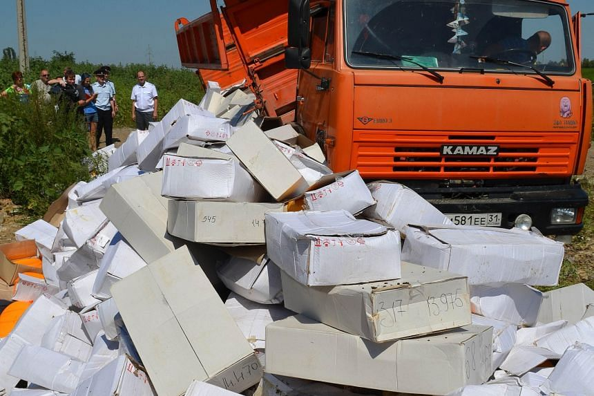 A truck dumping boxes of cheese outside the southern Russian city of Belgorod on Thursday. Prime Minister Vladimir Putin's order to destroy the food has caused a public outcry in Russia where many are struggling to feed themselves due to food price i