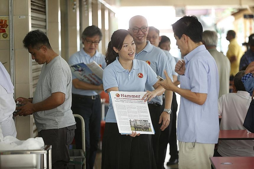 """Potential Workers' Party candidates He Ting Ru (centre, front) and Terence Tan (behind her) on a """"Hammer outreach"""" - selling the WP newsletter, the Hammer - during a walkabout at the Haig Road food centre yesterday."""