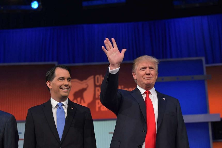 Donald Trump (right) and Scott Walker arrive on stage for the start of the Republican debate.