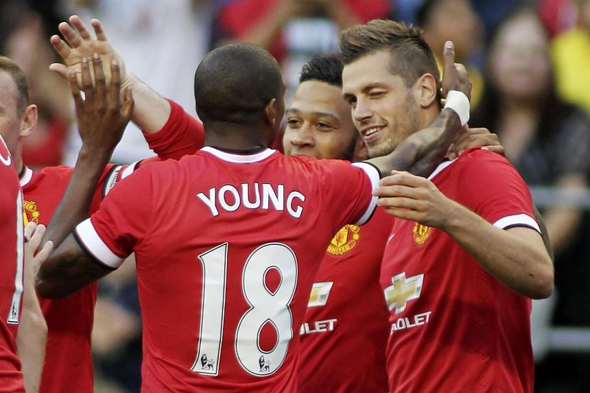 Manchester United's Morgan Schneiderlin (right) celebrating after scoring a goal with Ashley Young (left) and Memphis Depay (centre).