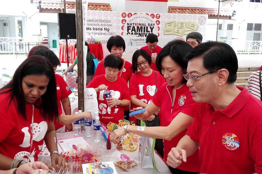 Tampines MPs Irene Ng (second from right) and Heng Swee Keat (right) interacting with residents during a National Day Family Carnival at Tampines Changkat on Friday.