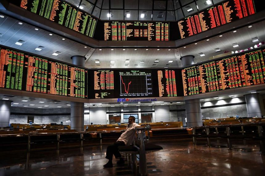 A man sitting before electronic boards showing stock movements at the Malaysia Stock Exchange in Kuala Lumpur.