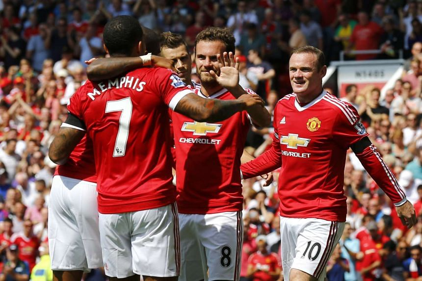 Manchester United's Wayne Rooney (right) celebrating with teammates after Kyle Walker's own goal.
