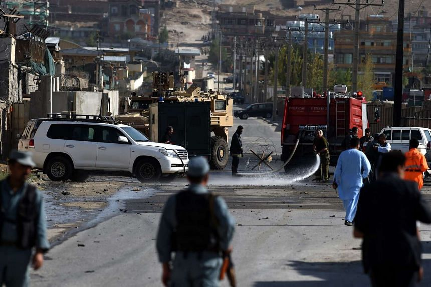 Afghan firefighters hose down the street outside Camp Integrity, a base housing US special forces that was attacked by militants, in Kabul on August 8, 2015.