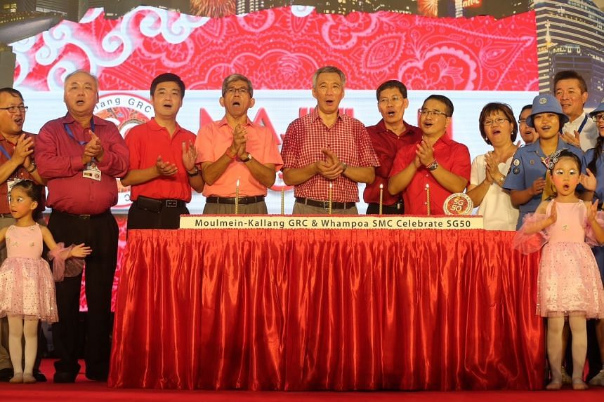PM Lee (centre), flanked by Kallang-Moulmein and Whampoa MPs, singing a birthday song for Singapore at the dinner.
