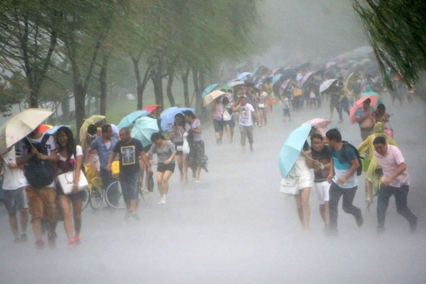 People in China's Zhejiang province running for shelter yesterday as Typhoon Soudelor approached. Across the strait, Taiwan evacuated thousands of people as torrential downpours lashed many parts of the island.
