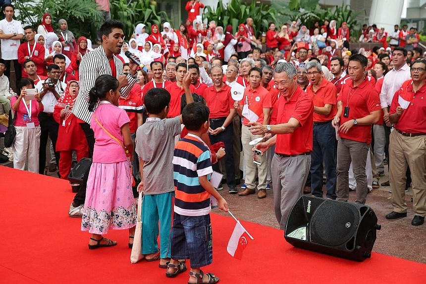 Prime Minister Lee Hsien Loong giving a Singapore flag to a child singing on stage at a National Day observance ceremony held at ITE College Central yesterday as host Shabir looked on. Also at the event were Malay MPs (behind PM Lee, from left) Senio