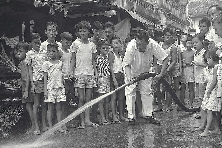 """Mr Lee Kuan Yew leading a mass spring-cleaning drive during National Loyalty Week in 1959. In the past, the waters of the Kallang Basin were murky, and the """"aroma"""" of the river was as local as the small vessels that plied the waterway carrying rice,"""