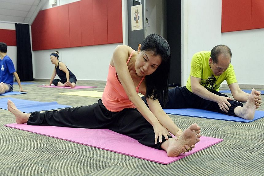 Financial consultant Ms Jeannie Bay and her husband Alvin Fok at a free pilates course at Kallang CC. They are among the 10,000 residents who have signed up for the 2,000 free courses offered by the People's Association which will run until the end o
