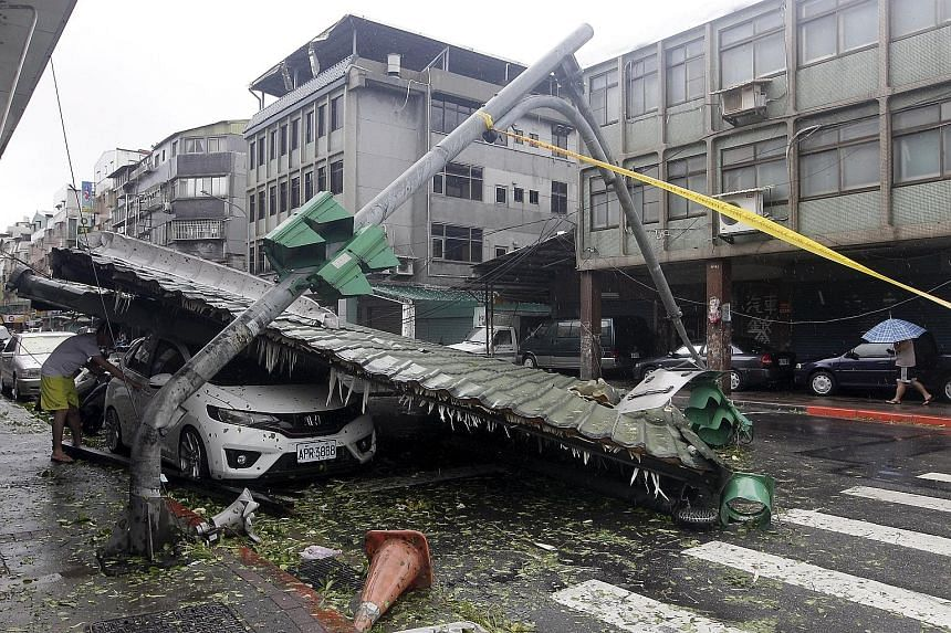 A man checking a car damaged by a fallen roof, next to a bent traffic light, in Taipei yesterday. Typhoon Soudelor's winds tore off roofs, signs and at least one bus stop from their fixtures.