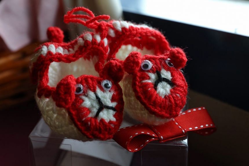 Pioneer Mrs A. Prasad presented a hand-knitted pair of SG50 booties that she made to the parents.
