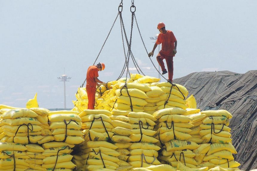 Workers unload goods waiting to be exported in a port in Lianyungang, east China's Jiangsu province.