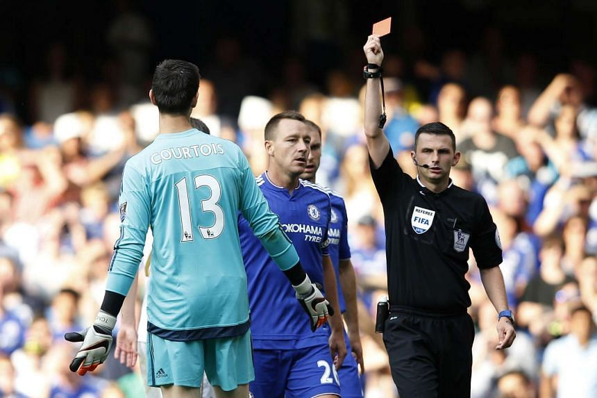 Referee Michael Oliver shows the red card to send off Chelsea's Belgian goalkeeper Thibaut Courtois.