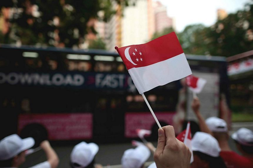 A Singapore flag is held up high during a National Day Observance Ceremony in Singapore.