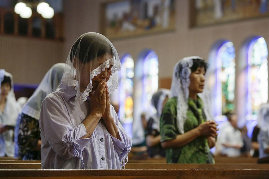 Nagasaki resident offering prayers during an early morning mass for victims of the atomic bombing of Nagasaki City in 1945 at Urakami Cathedral in Nagasaki, southwestern Japan on Aug 9, 2015.