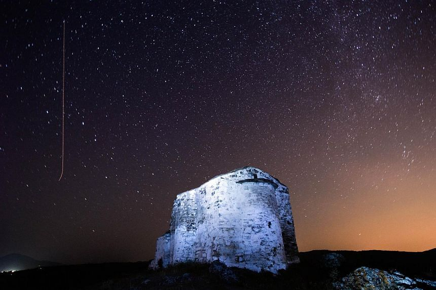 This file photograph taken late on Aug 12, 2013 shows a long exposure picture showing the sky at night during a Perseid meteor (left) shower, with a meteor streaking across the sky (left) over St Ioan medieval church near the village of Potsurnentsi.