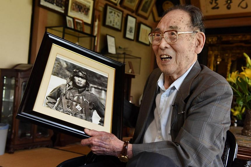 In this photograph taken on June 25, 2015, former Japanese fighter pilot Kaname Harada, 98, holds his portrait when he was young as he tells his experience during World War II at his home in Nagano, Nagano Prefecture.