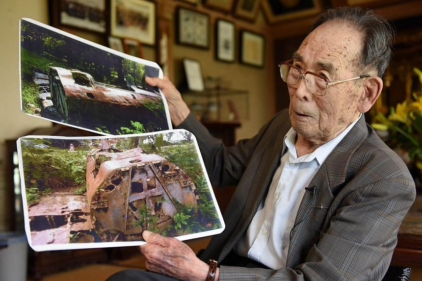 In this photograph taken on June 25, 2015, former Japanese fighter pilot Kaname Harada, 98, shows photographs of the rusting remains of his aircraft as he tells his experience during World War II at his home in Nagano, Nagano Prefecture.