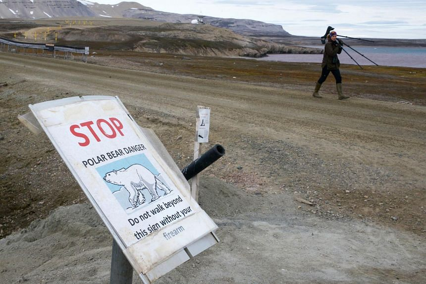 A scientist walking past a warning sign reading 'stop, polar bear danger, do not walk beyond this sign without your firearm', at the entrance of the scientific base of Ny Alesund in the Svalbard archipelago.