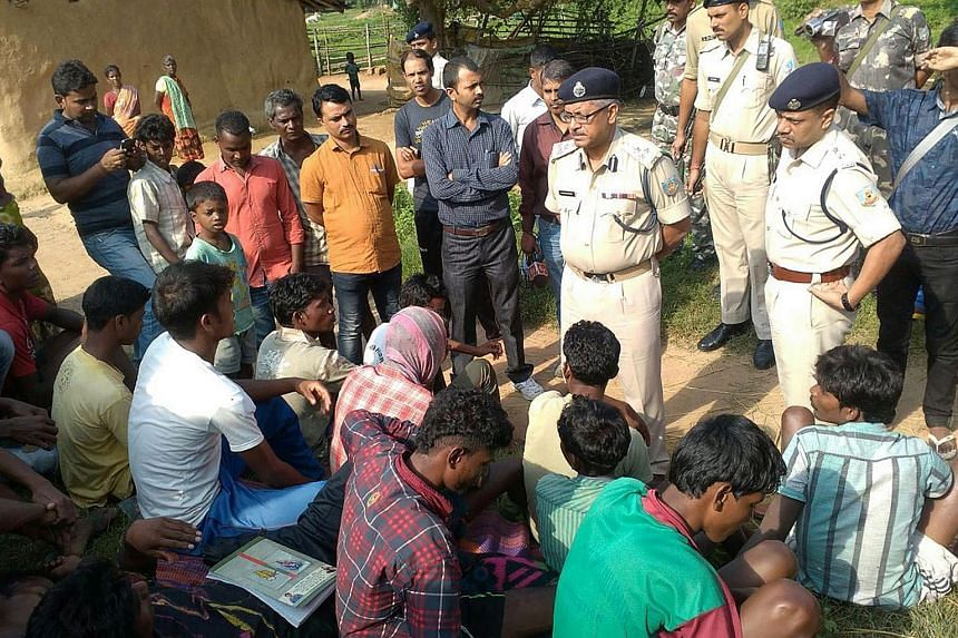 Indian police talk to villagers after five women were killed as they accused of practicing witchcraft in Kanjia village in eastern Jharkhand state on Aug 8, 2015.