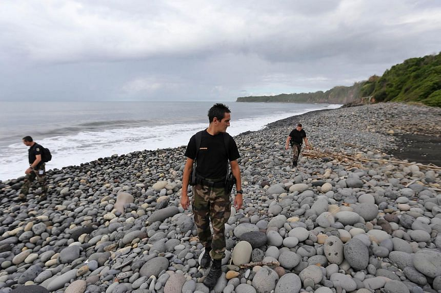 Police officers from Saint-Benoit's gendarmerie look for debris from the ill-fated Malaysia Airlines flight MH370 on a beach in Sainte-Marie de la Reunion, on Aug 8, 2015.