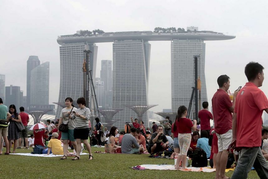 The MBS integrated resort is seen behind a crowd of revelers gathering on the Marina Barrage to watch an aerobatic show by the 'Black Knights' team during the jubilee weekend in Singapore on Aug 8, 2015.