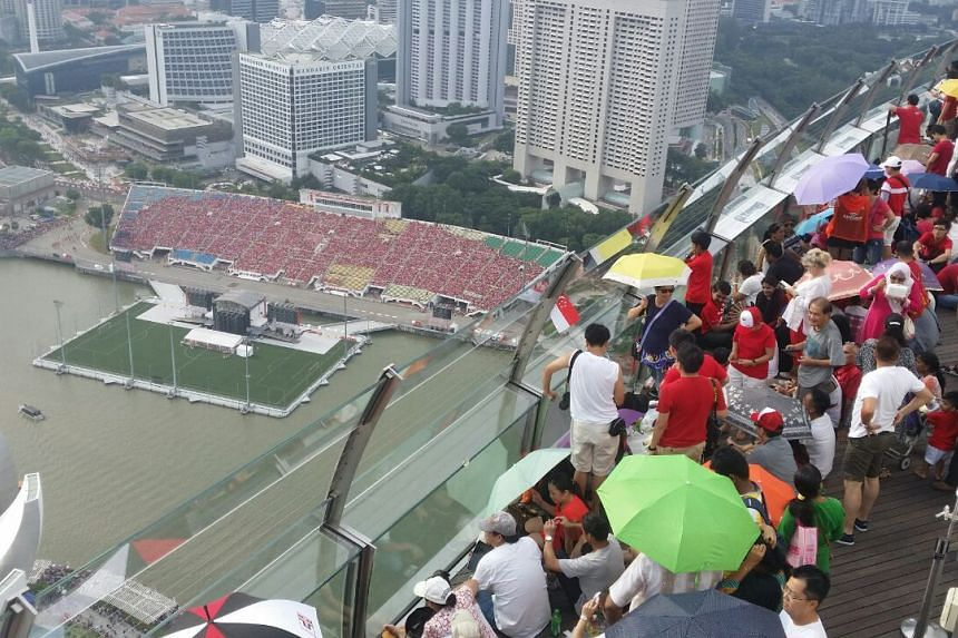 Hundreds of people have taken up seats at the SkyPark observation deck on the 56th floor of Marina Bay Sands for a good view of the floating platform. ST PHOTO: PRISCILLA GOY