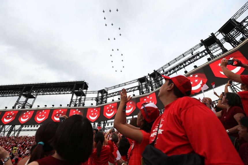 Singaporeans at the Padang rise to their feet as 20 F-16 fighter jets forming the number 50 fly overhead at a speed of 600km/h. ST PHOTO: SEAH KWANG PENG