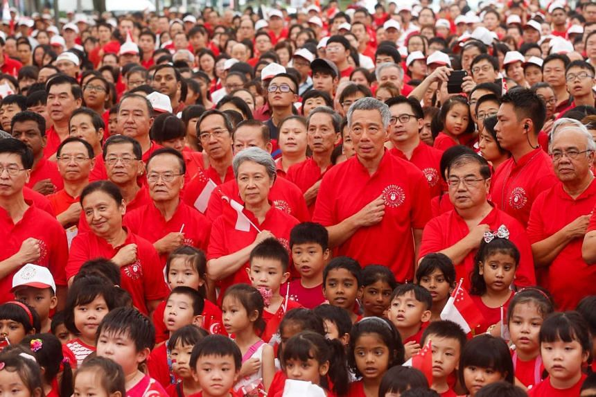 Prime Minister Lee Hsien Loong (middle row, third from right) with his wife Ho Ching (middle row, fourth from right) reciting the pledge at Teck Ghee in Ang Mo Kio on Aug 9, 2015.