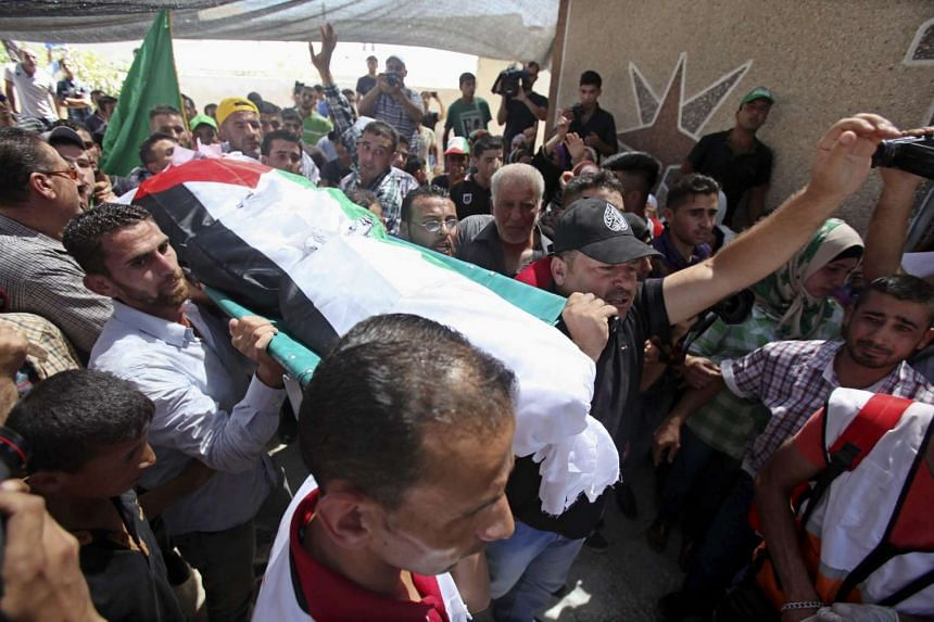 Palesinian family members carrying the body of Saad Dawabsha, during his funeral at his West Bank village of Douma near Nablus City, on Saturday. Saad is the father of the Palestinian infant killed in firebomb attack by suspected Jewish extremist in