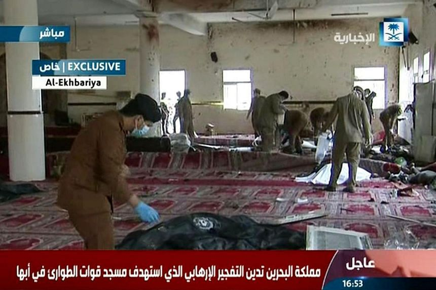 Saudi security forces inspecting the site of a suicide bombing at a mosque in the city of Abha, in this image grab taken from Saudi Al-Ekhbaria TV on Aug 6, 2015.