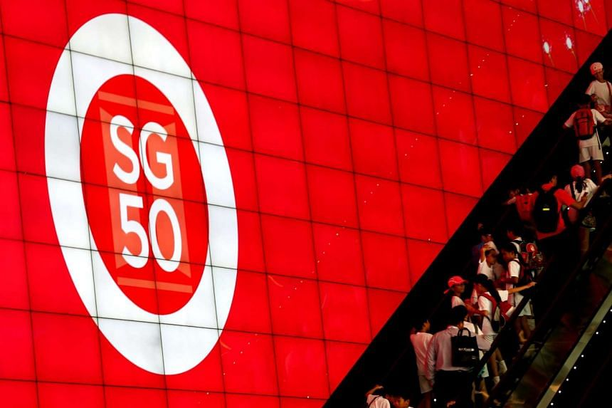 Students ride on an escalator next to the SG50 logo during the National Day Parade preview.