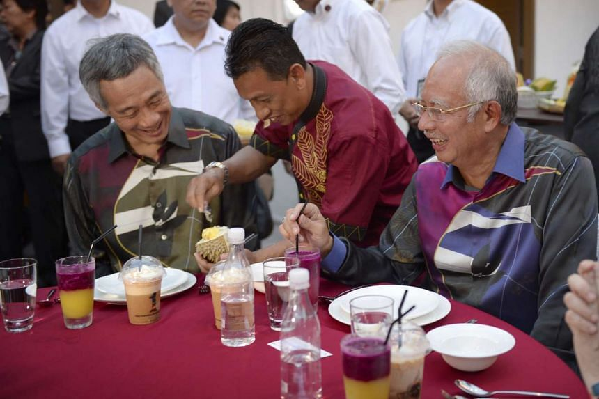 Prime Minister Lee Hsien Loong and his Malaysian counterpart Najib Razak being served top-grade Mao Shan Wang durian at the official opening of the Agrobazaar Malaysia in August last year. As Singapore and Malaysia mark 50 years of bilateral ties, th