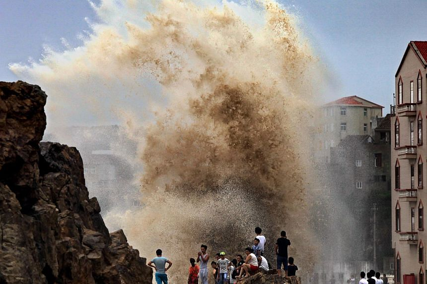 Residents gather to see huge waves stirred up by strong wind as typhoon Soudelor draws near the mainland of China on Aug 8, 2015.