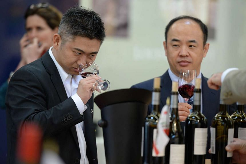 Visitors sample the bouquet of red wine at a stand of the Vinexpo wine festival in Bordeaux in June 2015.