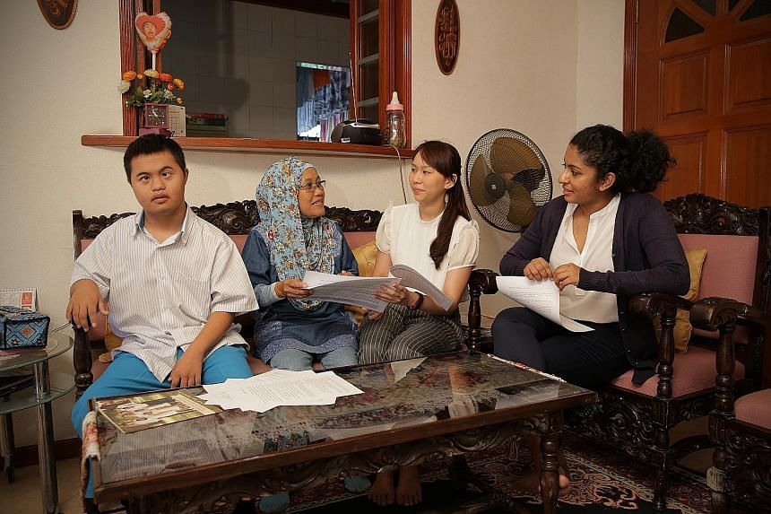 Helping Madam Halela Mawardi (second from left) with the application forms for a deputyship order to manage the affairs of her teenage son Muhammad Muhyiddin (far left) when he turns 21 are law undergraduates Kerri Tan and Mehaerun Simaa.