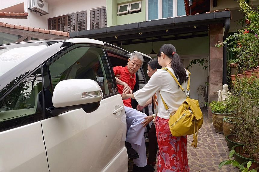 Former labour minister Jek Yeun Thong being helped into the car yesterday by his granddaughter Amelia Jek, 24, and daughter-in-law May Jek, 52, before heading to the National Day Parade, where he was honoured, along with two other Old Guard ministers