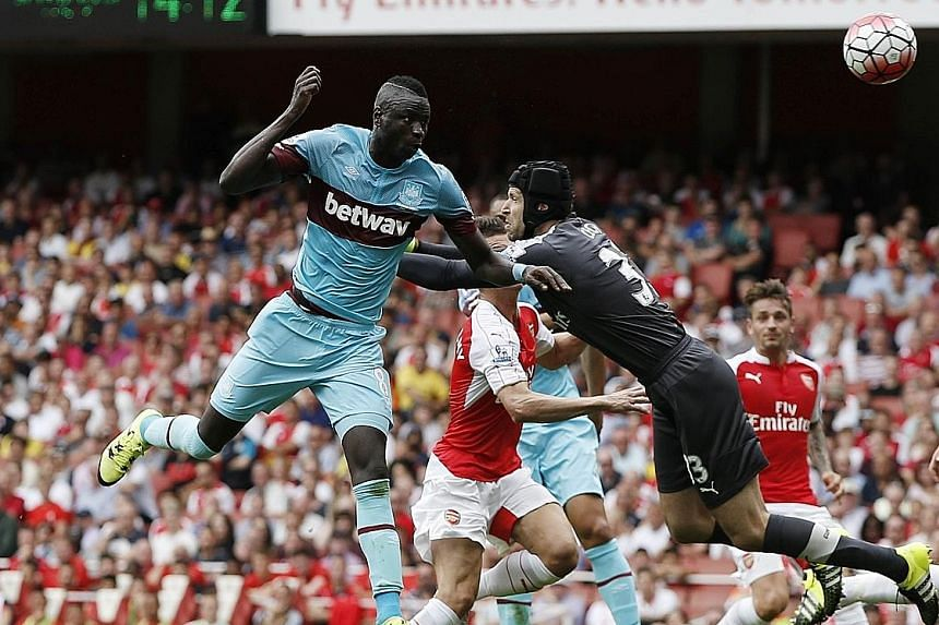 West Ham's Senegalese midfielder Cheikhou Kouyate gets to the ball ahead of Arsenal goalkeeper Petr Cech to head in the opening goal. Argentinian Mauro Zarate sealed the points in the second half.