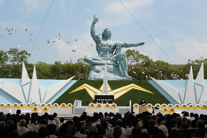 Doves flying over the Peace Statue during a memorial ceremony to mark the 70th anniversary of the atomic bombing of Nagasaki yesterday.