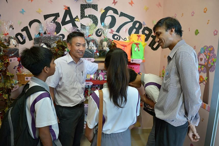 NorthLight School principal Martin Tan (left) and mathematics teacher Raj Kumar Naidu Rajamoney with students at the school's gift shop before its official opening last week. Mr Tan, who became the school's principal in 2011, says he empathises with
