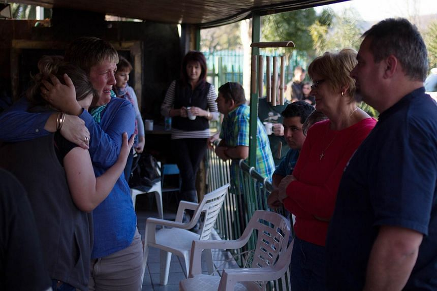 Carina Janse Van Rensburg (left) is comforted by family members on Aug 9, 2015 at her home in Pretoria, South Africa, after her husband Jaco Janse Van Rensburg was killed in the Byblos Hotel siege in Mali on Aug 7.
