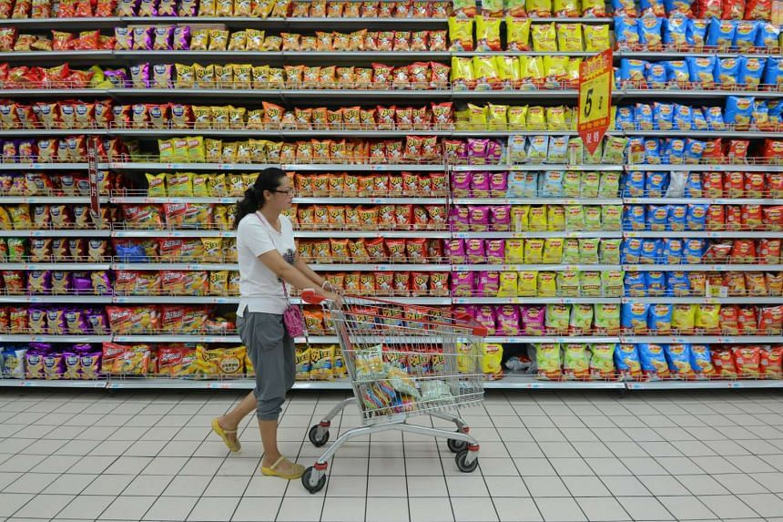 A customer shops for groceries at a supermarket in Fuyang, eastern China's Anhui province on Aug 9, 2015.