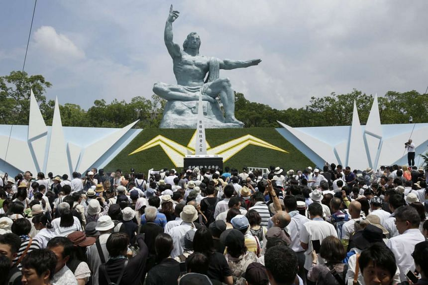 People gather around the Peace Prayer statue to offer prayers for victims killed by the atomic bombing of Nagasaki at the Nagasaki Peace Park on Aug 9, 2015.