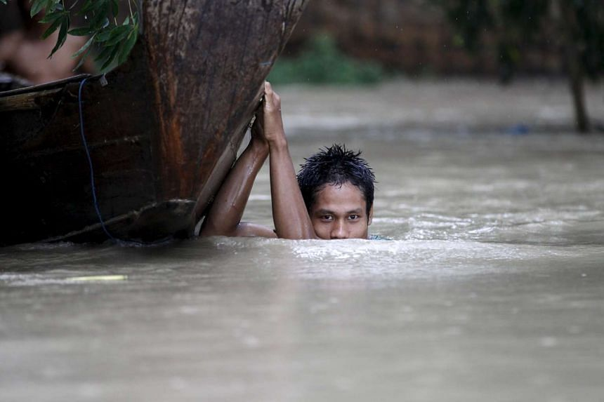 A boy moves his boat in a flooded village outside Zalun township, in the Irrawaddy delta, Myanmar, on Aug 6, 2015.